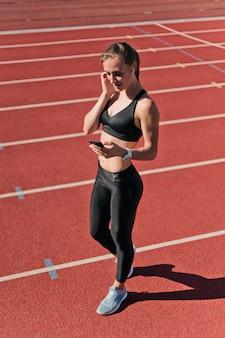 Молодая здоровая женщина в спортивной одежде слушает музыку в наушниках и использует смартфон на красной дорожке стадиона на улице