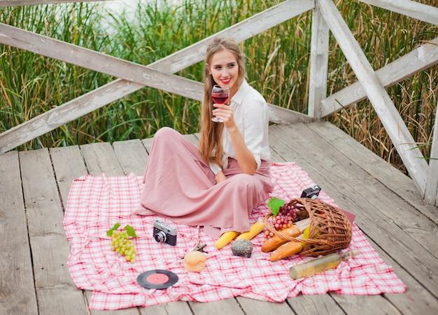Красивая молодая белокурая женщина в винтажных ретро одеждах имея пикник на деревянном пирсе самостоятельно. французский стиль пикник на природе