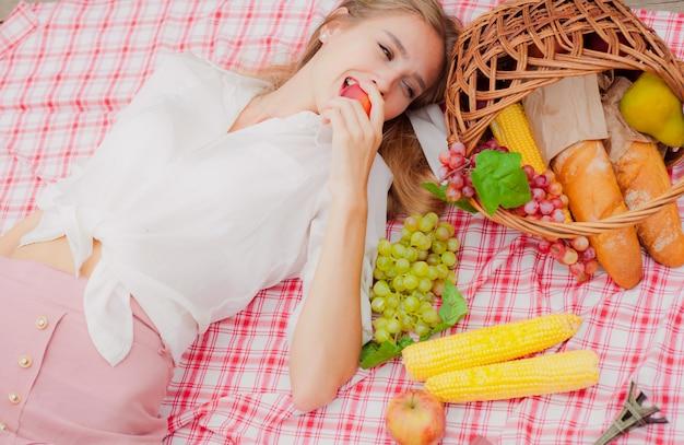 Молодая жизнерадостная белокурая женщина в винтажной одежде лежит на скатерти для пикника на открытом воздухе