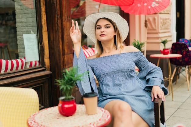 Молодая женщина в шляпе и платье кормит за столом в уличном кафе и жестом просит подойти к официанту