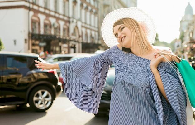 若い女性のジェスチャーで車をキャッチし、市内の道路で電話で話しています。ヒッチハイクのコンセプト