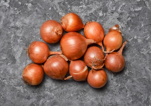 灰色のコンクリート表面に多くの玉ねぎ。有用な野菜。