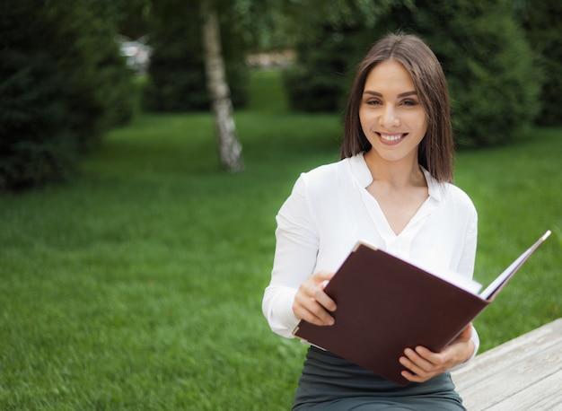 公園のベンチに座っている間彼女の手でドキュメントとフォルダーを保持している若い陽気な女性マネージャー。