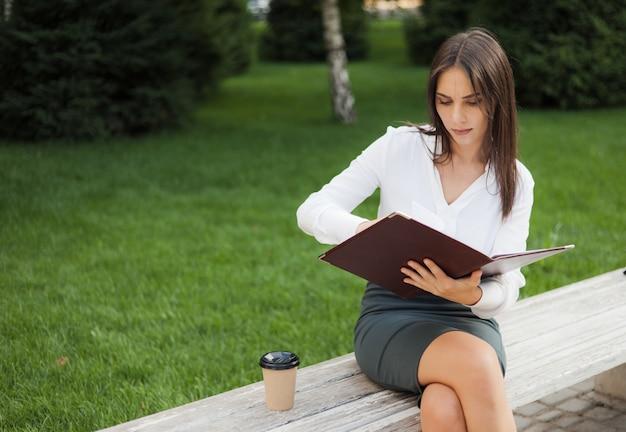 公園のベンチに座っている間彼女の手でドキュメントとフォルダーを保持している若い女性マネージャー。