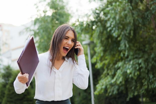 白いブラウスにスカートをまとったヒステリックな腹が立つビジネスウーマン、市内の屋外に書類のあるフォルダーを保持しながら電話で叫ぶスカート