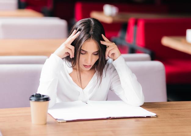 Молодая деловая женщина сидит за столом в кафе