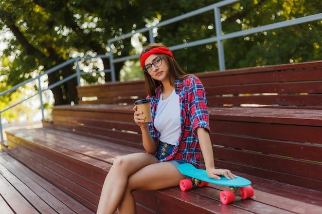 スタイリッシュな服を着た若い女性スケーターはスケートパークのスタンドに座って、明るい晴れた日にコーヒーを飲む