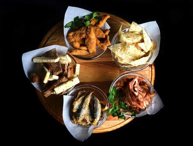 木の板にガラス製品でビールの軽食。チップス、スナック、ラスク、干し肉、魚のフライ。