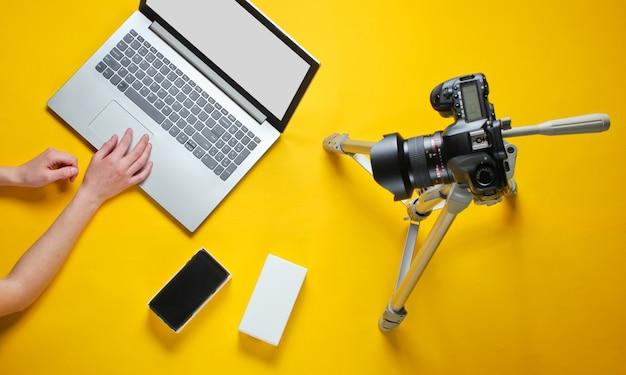 女性の手がボックスで新しいスマートフォンのボックス化を解除し、三脚にカメラでブログを書く