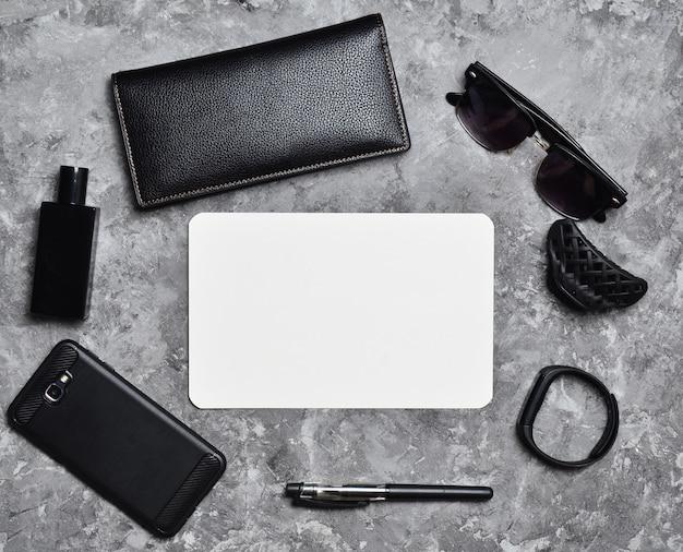 Рабочее пространство. аксессуары для деловой женщины на бетонном столе. пространство для текста. кошелек, лист бумаги, духи, солнцезащитные очки, умные часы, смартфон, ручка. тенденция минимализма. вид сверху.