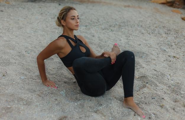 野生のビーチで砂の上に座ってストレッチ脚を行う陽気な若いフィット女性