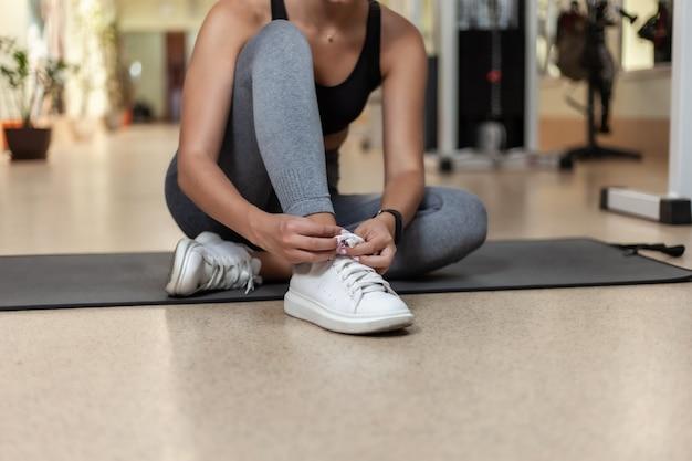 Женщина детенышей подходящая связывая шнурки спортивной обуви пока сидящ на циновке в спортзале. кадрировать фотографию
