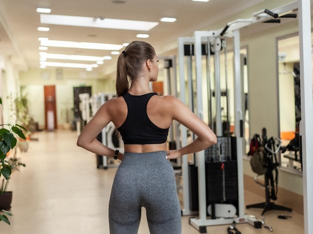 ジムでポーズのスポーツウェアで若いスリムスポーツ女性ボディービルダー。背面図