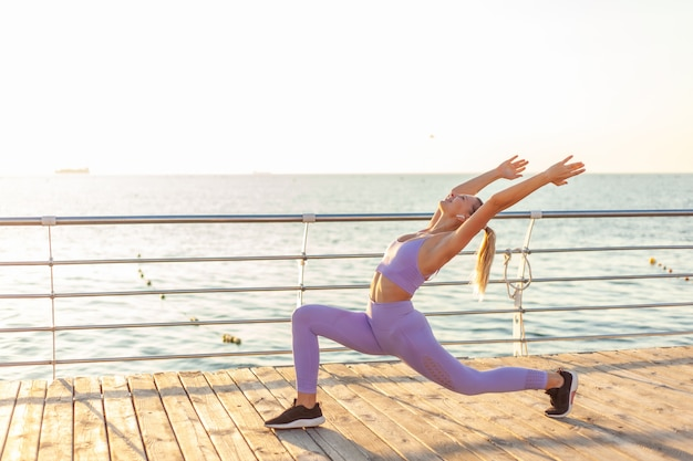 ヨガの練習。日の出のトレーニング。ビーチでアーサナ運動をしている若いスリムな女性。健康的なライフスタイルのコンセプト