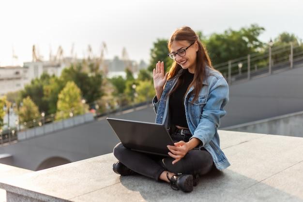 オンライン通話。デニムジャケットの若い女性学生は、屋外の街の階段に座っている間にオンラインブロードキャストを行います。通信教育