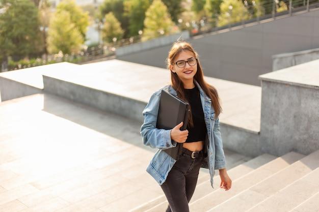 Молодая студентка в джинсовой куртке и очках поднимается по лестнице с ноутбуком в руках в городе