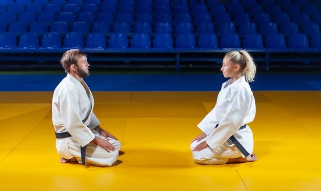 Боевые искусства. щадящие портнеры. спорт мужчина и женщина приветствуют друг друга, сидя в спортивном зале