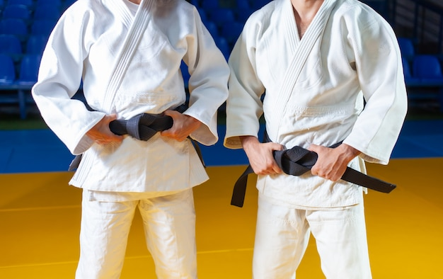 Два мастера спорта по дзюдо в белом кимано с черным поясом. кадрировать фотографию