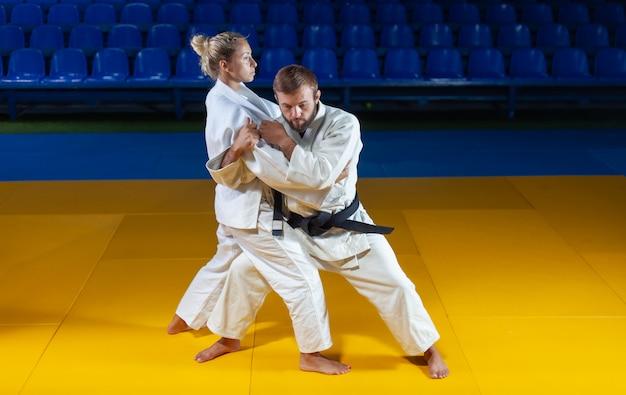 Боевые искусства. щадящие портнеры. спорт мужчина и женщина в белом кимоно тренируют броски дзюдо и захваты в спортивном зале