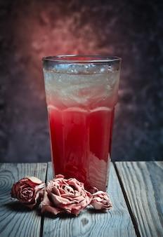ベリージュース、ウォッカ、ジン、テキーラ、コンクリートの壁の背景に木製のテーブルのラム酒と長い自家製アルコールカクテル。ドライローズ。
