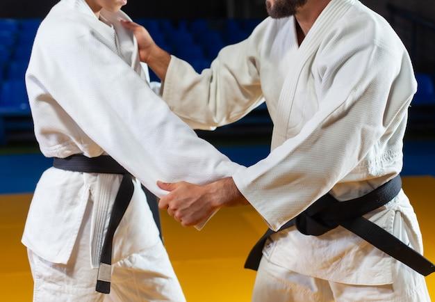 Боевые искусства. щадящие портнеры. спорт мужчина и женщина в белом кимоно поезд захватывает дзюдо в спортивном зале. кадрировать фотографию