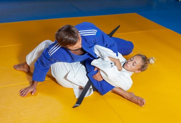 Боевые искусства. щадящие портнеры. спорт мужчина и женщина в бело-голубом кимоно тренирует дзюдо, бросает и захватывает в спортивном зале