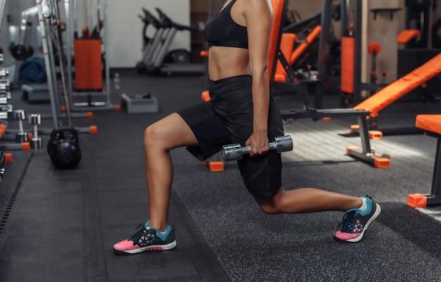 ジムで彼女の手にダンベルで突進を練習するスポーツウェアでスリムフィットの女性。フリーウェイトのトレーニングコンセプト。機能訓練