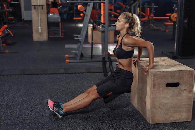 スポーツウェアの若い魅力的なスポーツ女性は、ジムで木箱で腕立て伏せを練習しています。機能トレーニングのコンセプト
