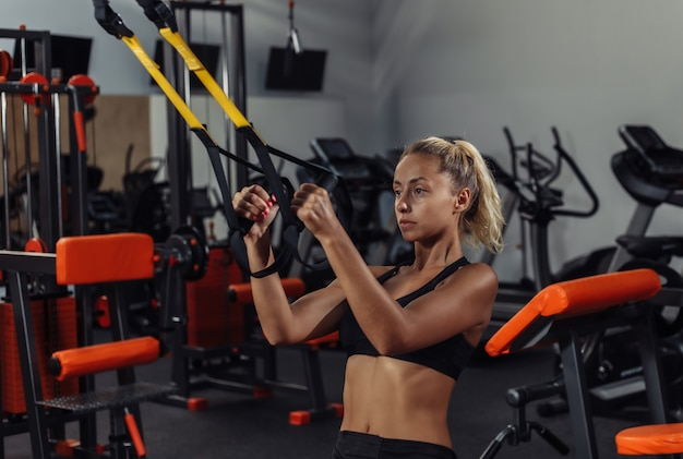 スポーツウェアの若い魅力的なスポーツ女性は、ジムでフィットネスストラップでトレーニングします。機能トレーニングのコンセプト