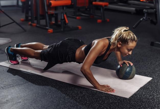 スポーツウェアの若い魅力的なスポーツ女性は、ジムで薬のボールで腕立て伏せを練習しています。機能トレーニングのコンセプト