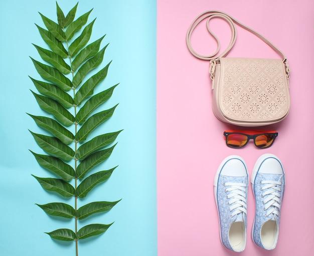 シダの葉、スニーカー、サングラス、パステルのバッグ。女性のアクセサリー、植物スタイル、トップビュー、フラットレイアウト