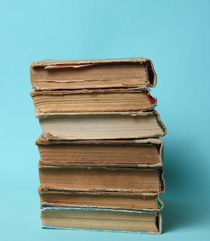 Стек старинных старых книг на синем