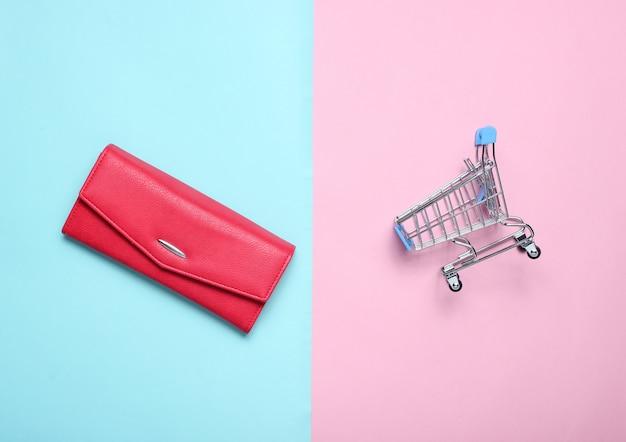 赤い女性の財布と色のパステルテーブル、消費者の概念、ミニマリズム、トップビューでの購入のためのミニショッピングトロリー。