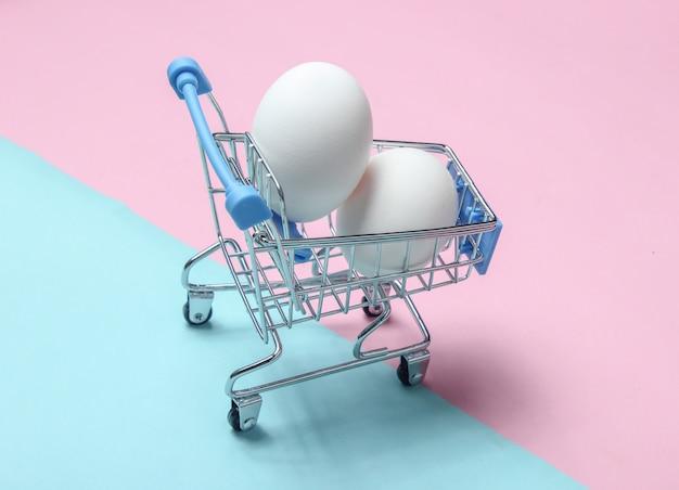 色付きのパステルテーブル、消費者の概念、ミニマリズム、トップビューでのショッピングのためのミニショッピングトロリーで鶏の卵。