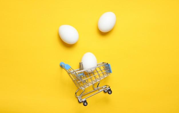 黄色のテーブル、消費者の概念、ミニマリズム、平面図でのショッピングのためのミニショッピングトロリーで鶏の卵。