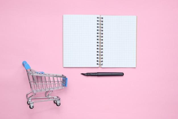 メモ帳、ピンクのパテルテーブルのショッピングカート。上面図。