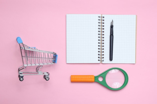 メモ帳、拡大鏡、ピンクのパテルテーブルのショッピングトロリー。