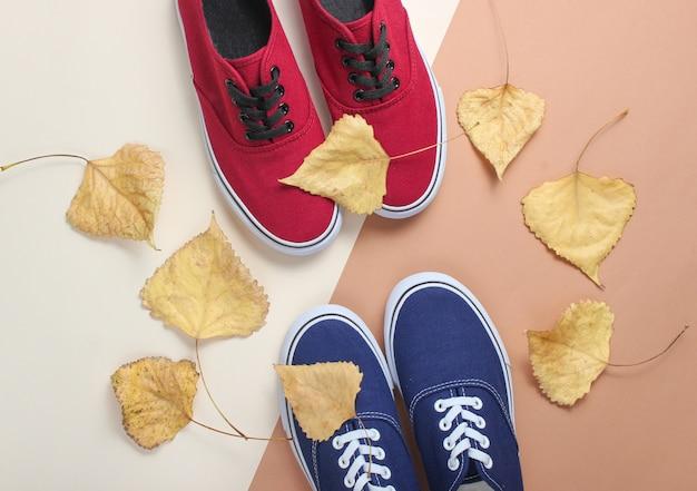 Синие и красные кроссовки и опавшие осенние листья. осенняя коллекция, модная женская обувь. вид сверху