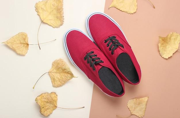 Красные кеды и опавшие осенние листья. осенняя коллекция, модная женская обувь. вид сверху