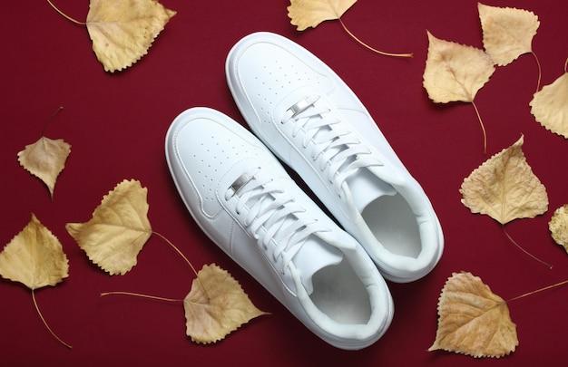 Белые кроссовки и опавшие осенние листья на бордовый стол. осенняя коллекция, модная обувь. вид сверху