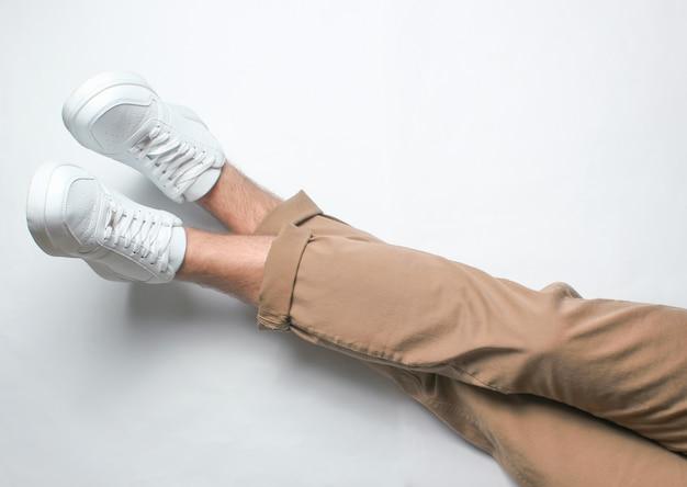 Фрагмент мужской ноги в бежевых брюках и белых кроссовках сидит. вид сверху. отдых