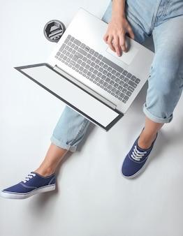 職場のオンライン従業員。ジーンズとスニーカーの女性の脚の断片。女性が座ってラップトップを使用しています。フリーランスのコンセプト。在宅勤務。