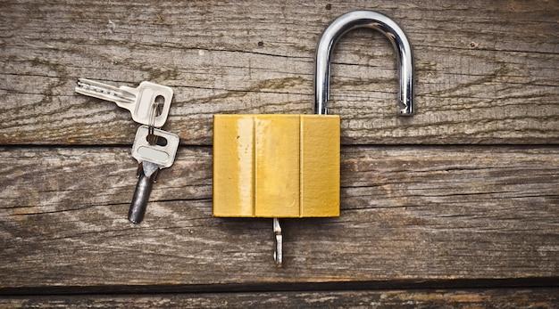 木製のテーブルのキーを持つ新しいロック。財産保護の概念。上面図。