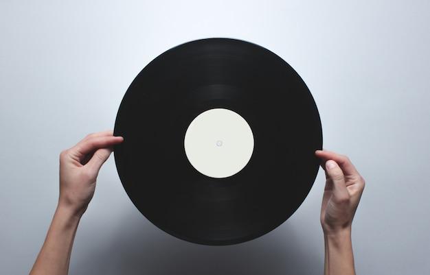 灰色のテーブルにレトロなビニールレコードを保持している女性の手。平面図、ミニマリズム。