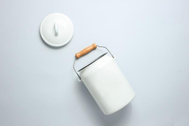 灰色のテーブルに白いエナメルミルク缶。上面図
