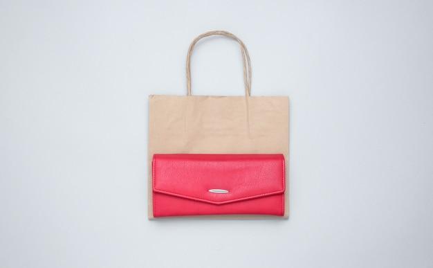 Бумажная хозяйственная сумка, красный кожаный бумажник на сером столе. вид сверху
