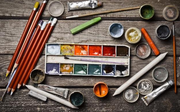 木製のテーブルに絵を描くことや創造性のための製品群。ガッシュ、油絵、水彩絵の具、クレヨン、鉛筆。上面図。平干し。