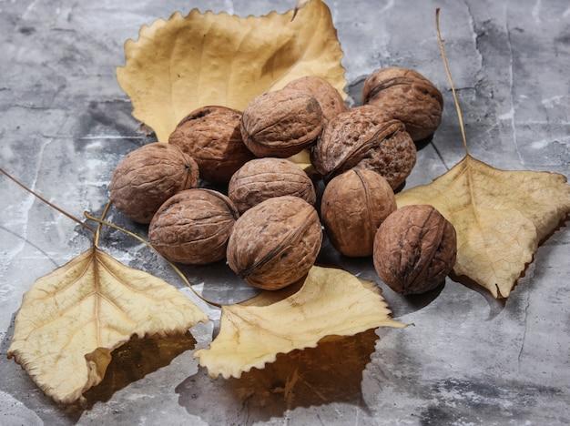 Грецкие орехи и опавшие осенние листья на сером бетонном столе