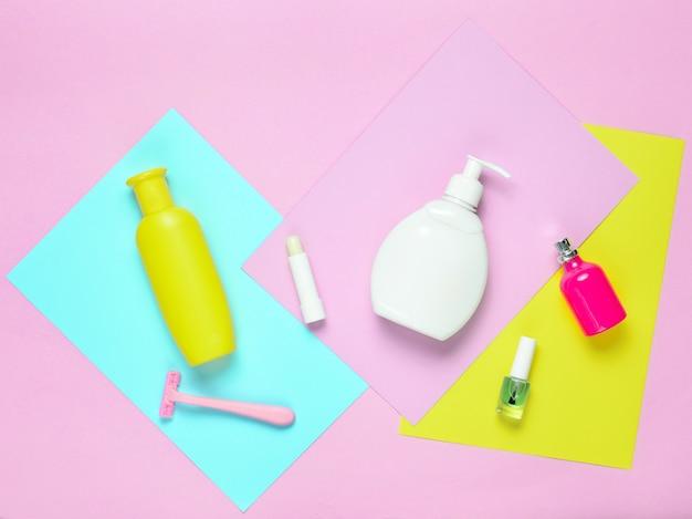 Товары для ухода за женской красотой на фоне цветной бумаги. бутылка шампуня, мыла, эпиляторная бритва, флакончик для духов, губная помада, лак для ногтей. вид сверху
