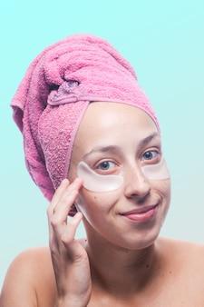 Усмехаясь молодая женщина с белыми заплатами под глазами и розовое полотенце на ее голове изолированной на сини. портрет крупным планом. уход за кожей